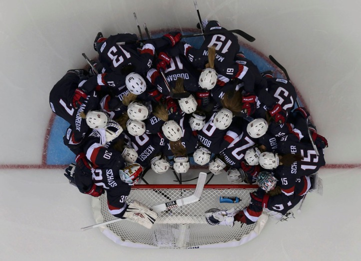 The U.S. women's hockey team huddles around the net before their preliminary round hockey game against Finland at the Sochi 2014 Winter Olympic Games